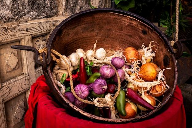 Vieux plat en cuivre avec ail, oignons et poivrons