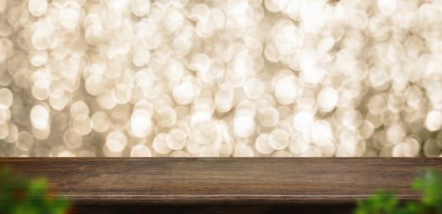Vieux plateau de table en bois sombre rustique avec flou bokeh doré et feuille flou