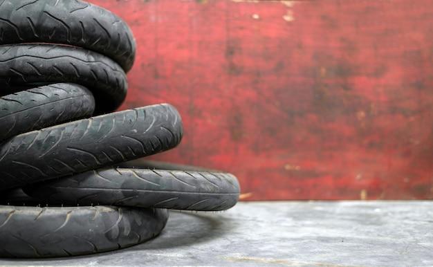 Vieux pneu de moto sur mur de briques rouges