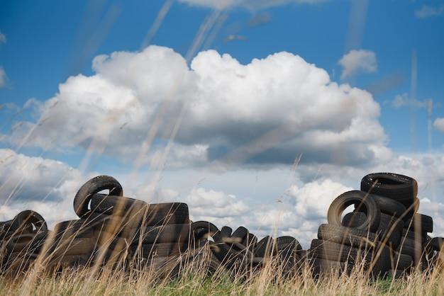 Vieux pneus usagés empilés avec de hautes piles