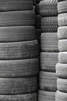Vieux pneus usés empilés avec de hauts pieux dans un garage de pièces de rechange de voiture