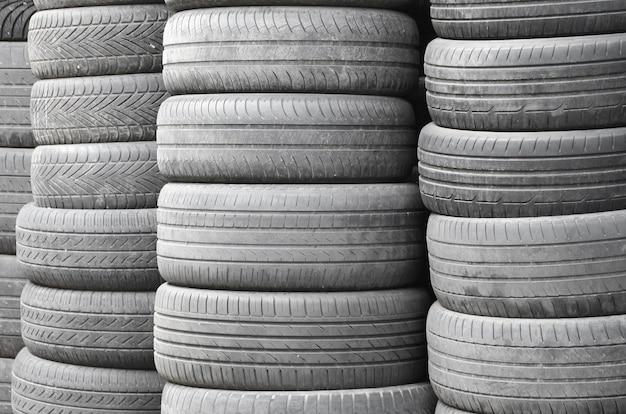 Vieux pneus usés empilés avec de hauts pieux dans un garage de pièces de rechange