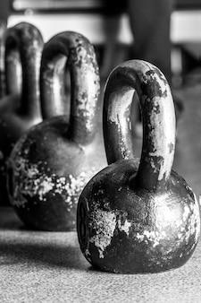 Vieux poids et haltères dans la salle de gym sur le sol.