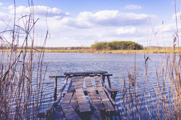 Vieux pont en bois près de la rivière sur le fond d'un beau ciel