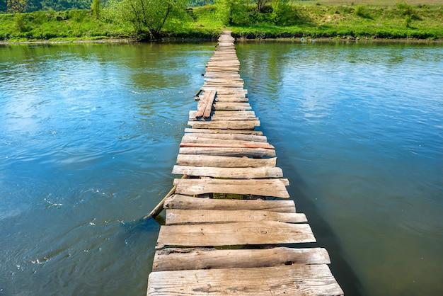 Vieux pont en bois à travers la rivière avec des arbres verts sur les rives