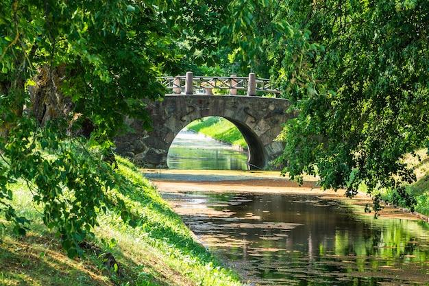 Vieux pont de pierre sur la rivière et feuillage vert luxuriant.