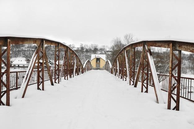 Vieux pont routier en acier sur la rivière après des chutes de neige