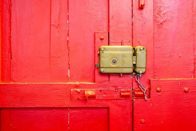 Vieux portail rouge avec serrure manuelle