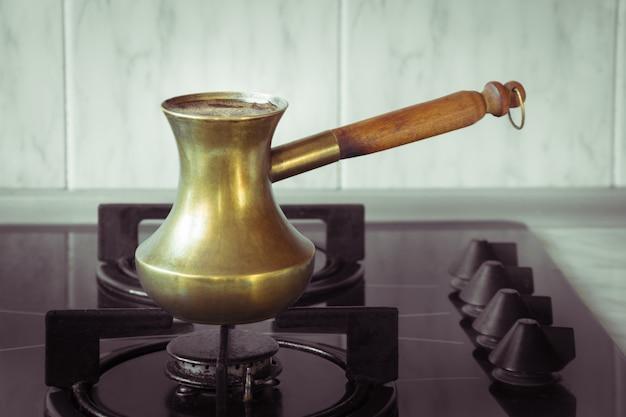 Vieux pot de cuivre turc pour la préparation du café sur la cuisinière petit déjeuner matinal méthode turque de préparation du café