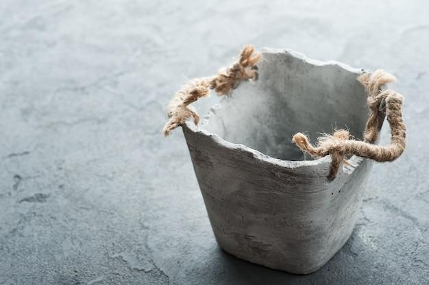 Vieux pot de fleur vide sur une table en béton