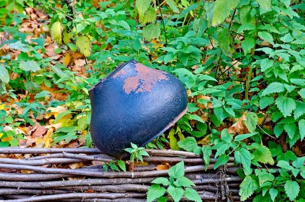 Vieux pot en fonte sur la clôture sur fond d'herbe verte et de feuilles d'automne jaunes