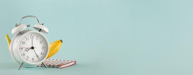 Vieux réveil banane bloc-notes fond clair copie espace. concept de l'éducation
