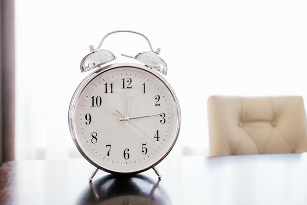 Vieux réveil rétro sur une table en bois avec fond pastel