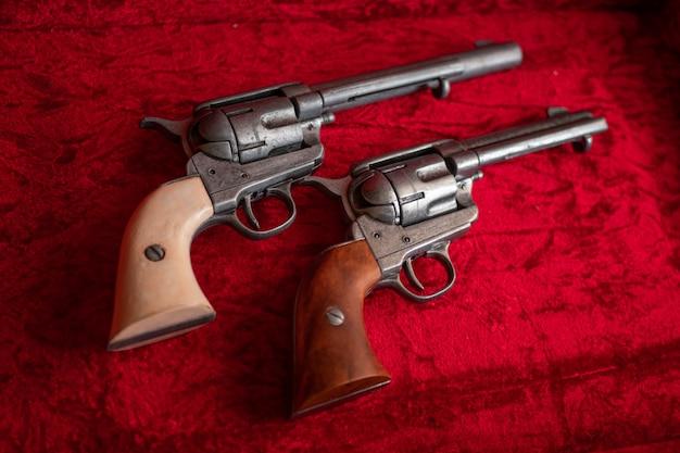 Vieux revolvers du far west avec poignées en bois marron et blanc sur velours rouge.