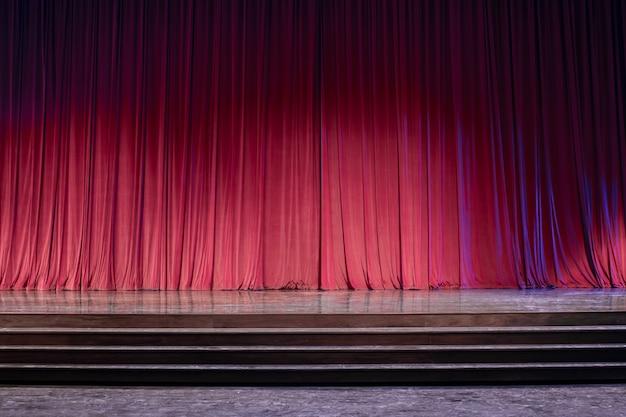 Vieux rideaux rouges sur scène.