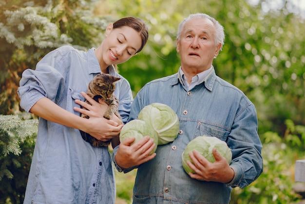 Vieux senior debout dans un jardin d'été avec du chou