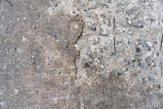 Vieux sol en béton fissuré qui laisse voir la pierre à l'intérieur du côté gauche.