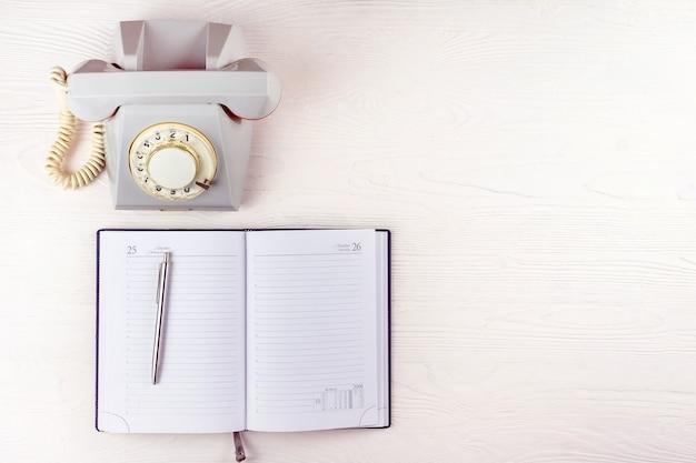 Vieux téléphone avec un cahier