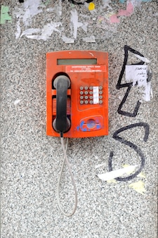 Vieux téléphone cassé dans une cabine téléphonique