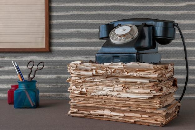 Vieux téléphone noir et fournitures de bureau