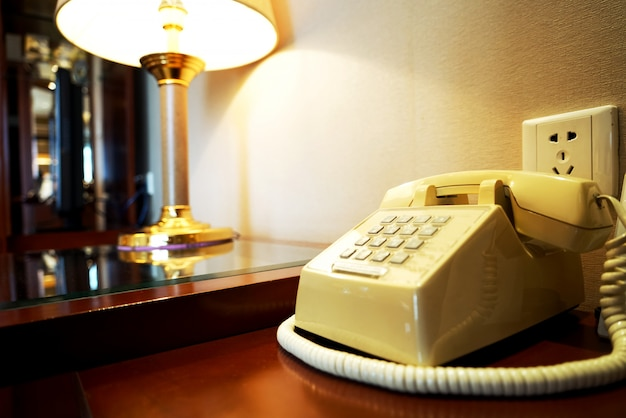 Vieux téléphone sur une table en bois près du mur et de la rampe dans une chambre d'hôtel