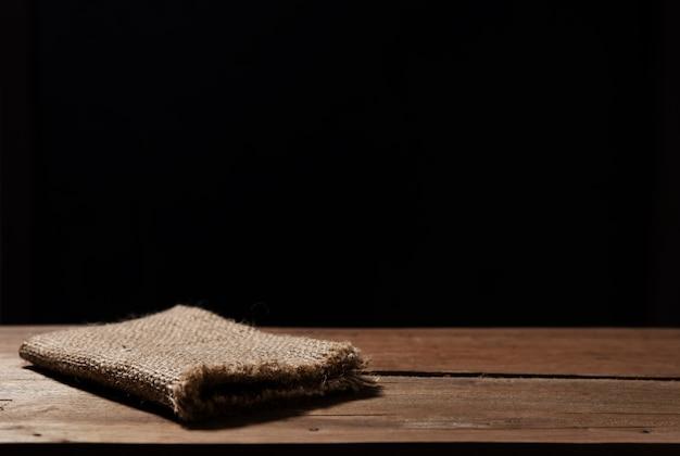 Vieux texture de bois sombre brun et sac en tissu avec un fond sombre pour la conception