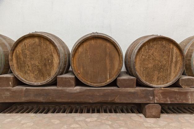 De vieux tonneaux de chêne se trouvent au sous-sol sur des rondins de bois, de vieilles caves à vin avec des bouteilles et des tonneaux