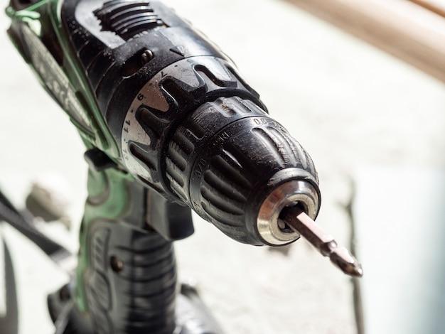 Le vieux tournevis électrique sale sur des batteries est dans l'atelier sur le matériel