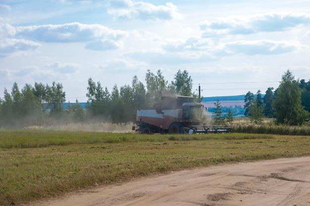 Le vieux tracktor laboure la moissonneuse de champ récolte le blé d'un champ agricole semé