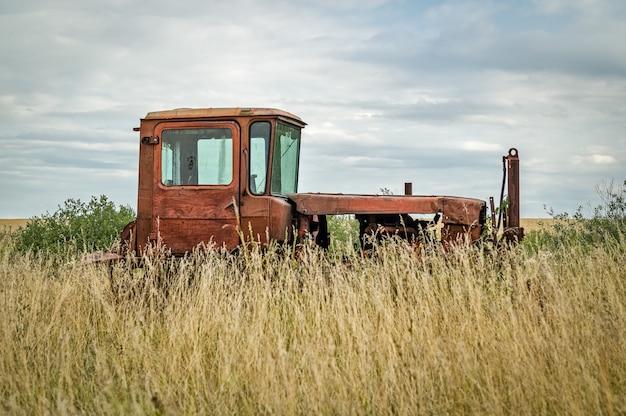 Vieux tracteur abandonné dans un champ envahi par les hautes herbes.