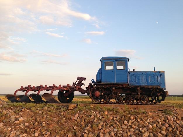 Vieux tracteur avec une charrue sur le terrain