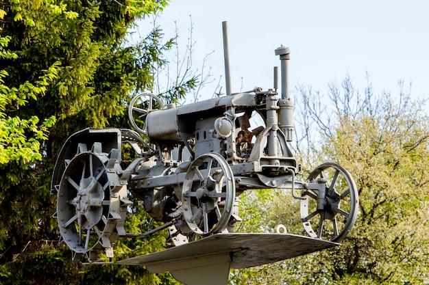 Vieux tracteur sur piédestal dans le musée en plein air