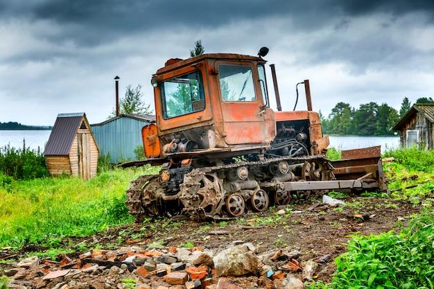 Vieux tracteur sale au bord de la rivière dans un paysage rustique.