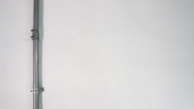 Vieux tuyau en acier argenté et mur de texture blanche et ombre.
