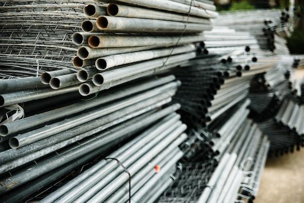 Vieux tuyaux en acier empilés dans un entrepôt industriel.