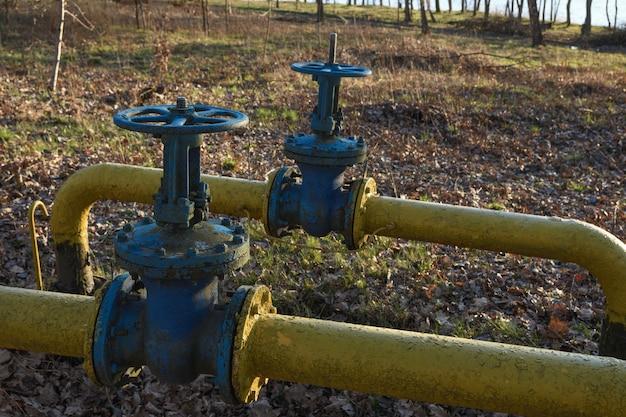 De vieux tuyaux de gaz avec de grands robinets qui se chevauchent sont posés sous terre dans la cour.