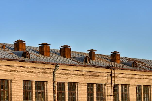 Vieux tuyaux de ventilation rouillés sur le toit d'un bâtiment à plusieurs étages