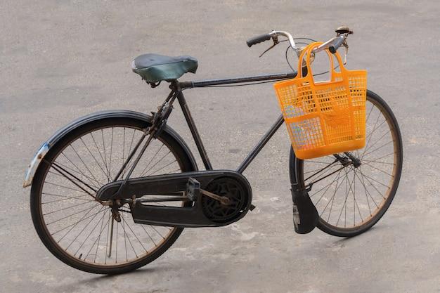 Le vieux vélo est debout dans la rue.