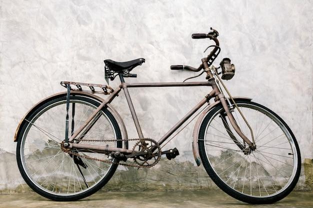 Vieux vélo vintage rouillé près du mur de béton