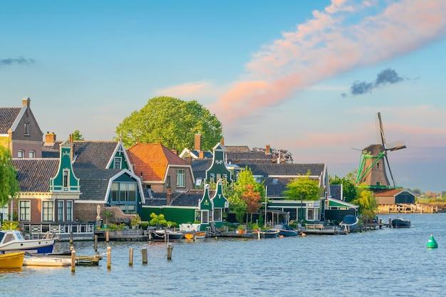 Vieux village traditionnel avec des moulins à vent hollandais à amsterdam, pays-bas au coucher du soleil