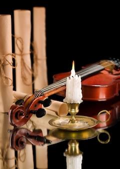 Vieux violon avec bougie et vieux rouleau de papier