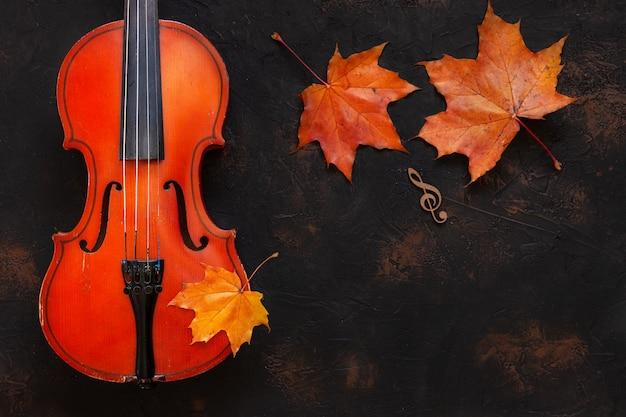 Vieux violon avec feuilles d'érable de l'automne jaune.
