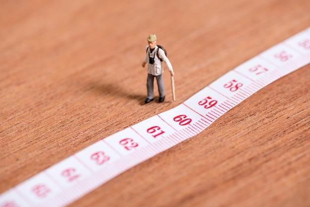 Vieux voyageur miniature avec 60e nombre d'âge sur un ruban à mesurer