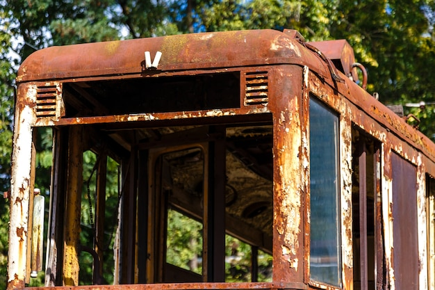 Vieux wagon détruit rouillé du tram à l'extérieur à la journée ensoleillée.