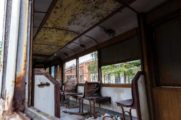 Vieux wagon rouillé de tram détruit à l'extérieur à la journée ensoleillée.