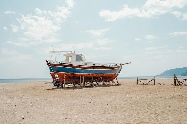 Vieux yacht abandonné solitaire sur une plage de sable vide en été photo de haute qualité