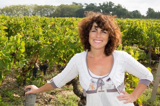 Vigneron, femme, debout, vigne, rangées