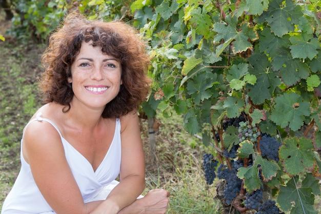 Vigneron femme heureuse et souriante en rangées de vigne