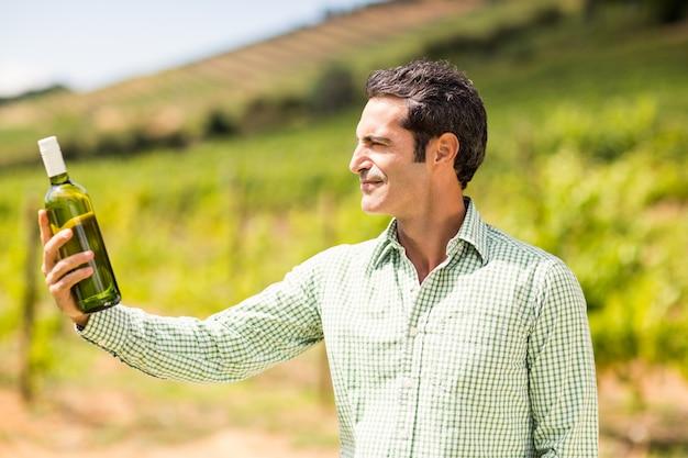 Vigneron souriant regardant la bouteille de vin