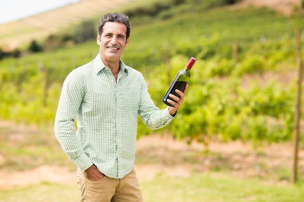 Vigneron souriant tenant une bouteille de vin